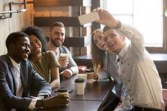 Amigos novos diversos que tomam o selfie no smartphone junto no Ca imagens de stock