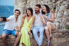 Amigos novos do turista com a tabuleta digital que tem o divertimento fotografia de stock