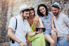 Amigos novos do turista com a tabuleta digital que tem o divertimento fotos de stock royalty free