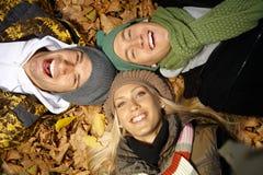 Amigos novos entre o sorriso das folhas de outono Fotografia de Stock Royalty Free