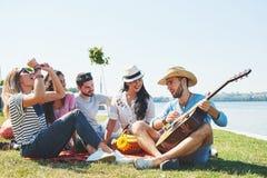 Amigos novos felizes que têm o piquenique no parque Estão tudo felizes, tendo o divertimento, sorrindo e jogando a guitarra Imagens de Stock Royalty Free