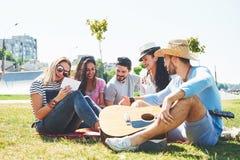 Amigos novos felizes que têm o piquenique no parque Estão tudo felizes, tendo o divertimento, sorrindo e jogando a guitarra Fotos de Stock