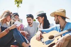 Amigos novos felizes que têm o piquenique no parque Estão tudo felizes, tendo o divertimento, sorrindo e jogando a guitarra Fotos de Stock Royalty Free