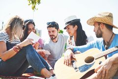 Amigos novos felizes que têm o piquenique no parque Estão tudo felizes, tendo o divertimento, sorrindo e jogando a guitarra Foto de Stock Royalty Free