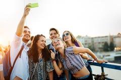 Amigos novos felizes que tomam o selfie na rua fotografia de stock