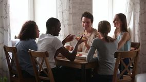Amigos novos multirraciais felizes que falam comendo a pizza que compartilha da tabela do café video estoque