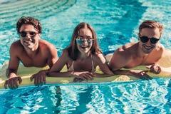 Amigos novos na piscina Fotografia de Stock Royalty Free