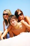 Amigos novos na praia do verão Imagem de Stock