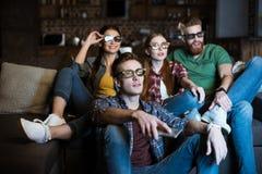 Amigos novos nos vidros 3D que olham o filme Imagens de Stock