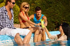 Amigos novos pelo sorriso da piscina imagens de stock