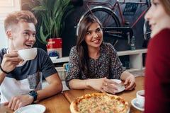 Amigos novos positivos que têm uma pausa para o almoço no café retro à moda Menino e meninas que têm uma grande estadia junto, fa Imagem de Stock