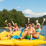 Estudantes novos que remam no tempo do divertimento da água Imagens de Stock