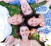 Amigos novos que dão forma a um círculo Foto de Stock Royalty Free