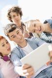 Amigos novos que fotografam-se através da tabuleta digital no campus universitário foto de stock
