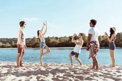 Amigos novos que jogam o voleibol no Sandy Beach no dia Foto de Stock Royalty Free