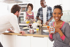 Amigos novos que preparam o pequeno almoço na cozinha imagem de stock royalty free