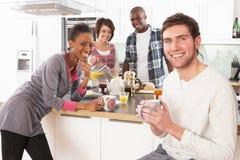 Amigos novos que preparam o pequeno almoço na cozinha Fotos de Stock Royalty Free