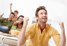 Amigos novos que prestam atenção à tevê em casa Imagens de Stock Royalty Free
