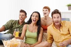Amigos novos que prestam atenção ao futebol em casa Imagem de Stock