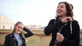 Amigos novos que têm um bom ar livre do tempo - um homem com cabelo longo para abrir uma garrafa com bebida do álcool filme