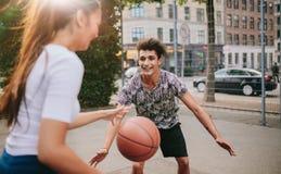 Amigos novos que têm um jogo do basquetebol Fotos de Stock