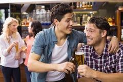 Amigos novos que têm uma bebida junto Foto de Stock