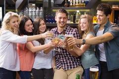Amigos novos que têm uma bebida junto Fotografia de Stock