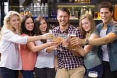 Amigos novos que têm uma bebida junto Imagem de Stock