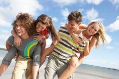 Amigos novos que têm o divertimento na praia do verão Fotografia de Stock Royalty Free