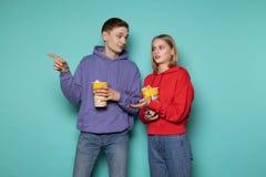 Amigos novos surpreendidos, menina loura no hoodie vermelho e seu amigo no hoodie roxo com pipoca nas m?os que aponta em imagem de stock