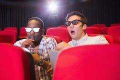 Amigos novos surpreendidos que olham o filme 3d Fotos de Stock