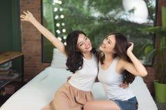 Amigos o adolescentes felices que se divierten y que saltan en cama en Imágenes de archivo libres de regalías