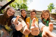 Amigos o estudiantes adolescentes que muestran los pulgares para arriba Fotos de archivo