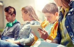 Amigos o estudiantes con PC de la tableta al aire libre Fotografía de archivo