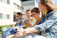 Amigos o estudiantes con PC de la tableta al aire libre Imagenes de archivo