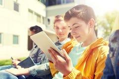 Amigos o estudiantes felices con PC de la tableta al aire libre Imagen de archivo libre de regalías