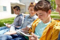 Amigos o estudiantes felices con PC de la tableta al aire libre Imagen de archivo