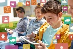 Amigos o estudiantes felices con PC de la tableta al aire libre Fotografía de archivo