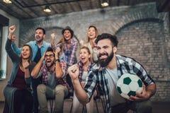 Amigos o fanáticos del fútbol felices que miran fútbol en la TV y que celebran la victoria fotos de archivo libres de regalías
