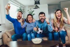 Amigos o fan?ticos del f?tbol que miran f?tbol en la TV y que celebran la victoria en casa Amistad, deportes y concepto del entre fotos de archivo libres de regalías