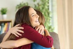 Amigos o hermanas que abrazan en casa Imagenes de archivo