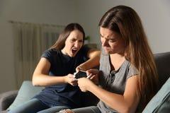 Amigos o hermanas que luchan para un teléfono elegante Imagen de archivo