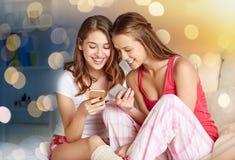 Amigos o muchachas adolescentes con smartphone en casa Imagen de archivo libre de regalías