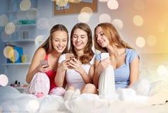 Amigos o muchachas adolescentes con smartphone en casa Imagenes de archivo