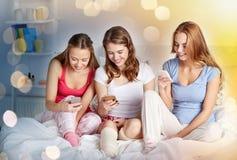 Amigos o muchachas adolescentes con smartphone en casa Fotos de archivo libres de regalías