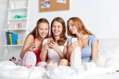 Amigos o muchachas adolescentes con smartphone en casa Foto de archivo libre de regalías