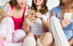 Amigos o muchachas adolescentes con smartphones en casa Imagen de archivo libre de regalías