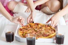 Amigos o muchachas adolescentes que comen la pizza en casa Fotos de archivo