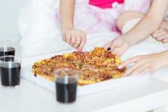 Amigos o muchachas adolescentes que comen la pizza en casa Imagenes de archivo