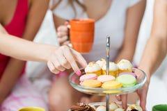 Amigos o muchachas adolescentes que comen los dulces en casa Imagen de archivo libre de regalías